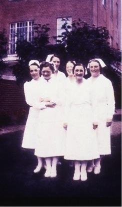 Ancienne photo en couleurs d'un groupe d'infirmières souriant devant un édifice de brique