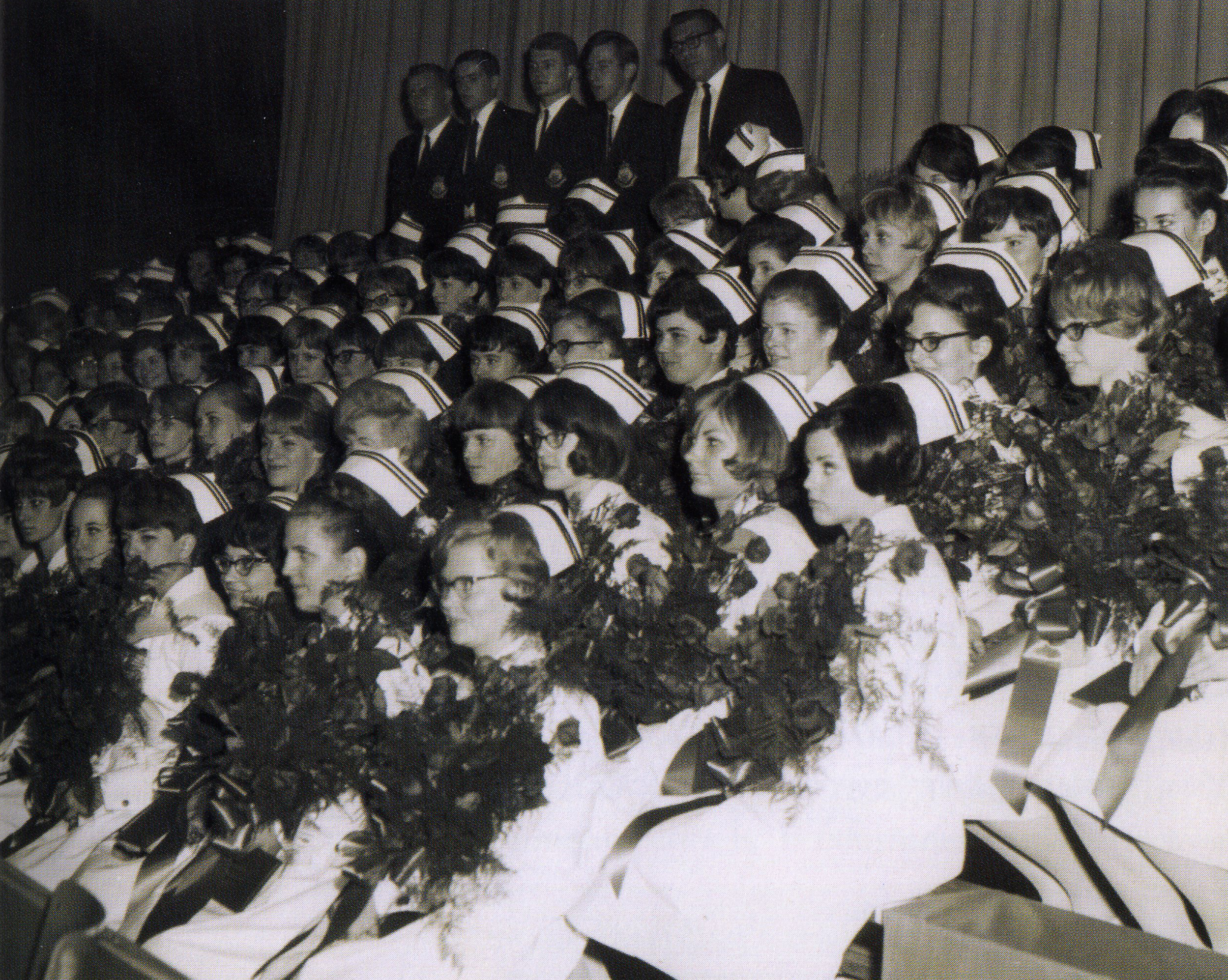 group of young nurses in uniform holding bouquets of flowers