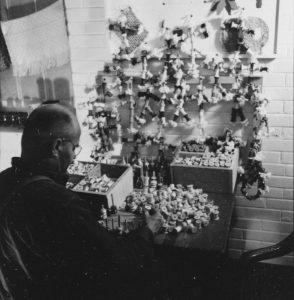 man sitting in from of large display of bobbins with wool on them