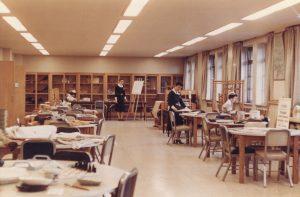 Photographie en couleurs des années 1950 représentant des femmes s'affairant à diverses activités dans une grande pièce avec des tables, des étagères et un chevalet