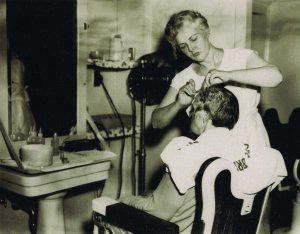 Photo ancienne d'une femme coiffant un homme dans un salon de coiffure