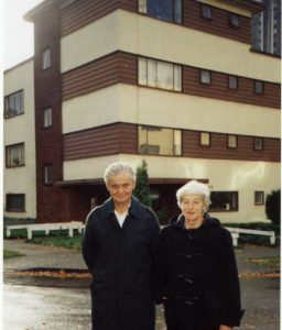 man and woman standing in front of an older apartment building