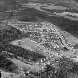 black and white aerial photograph of roads with houses and forested area
