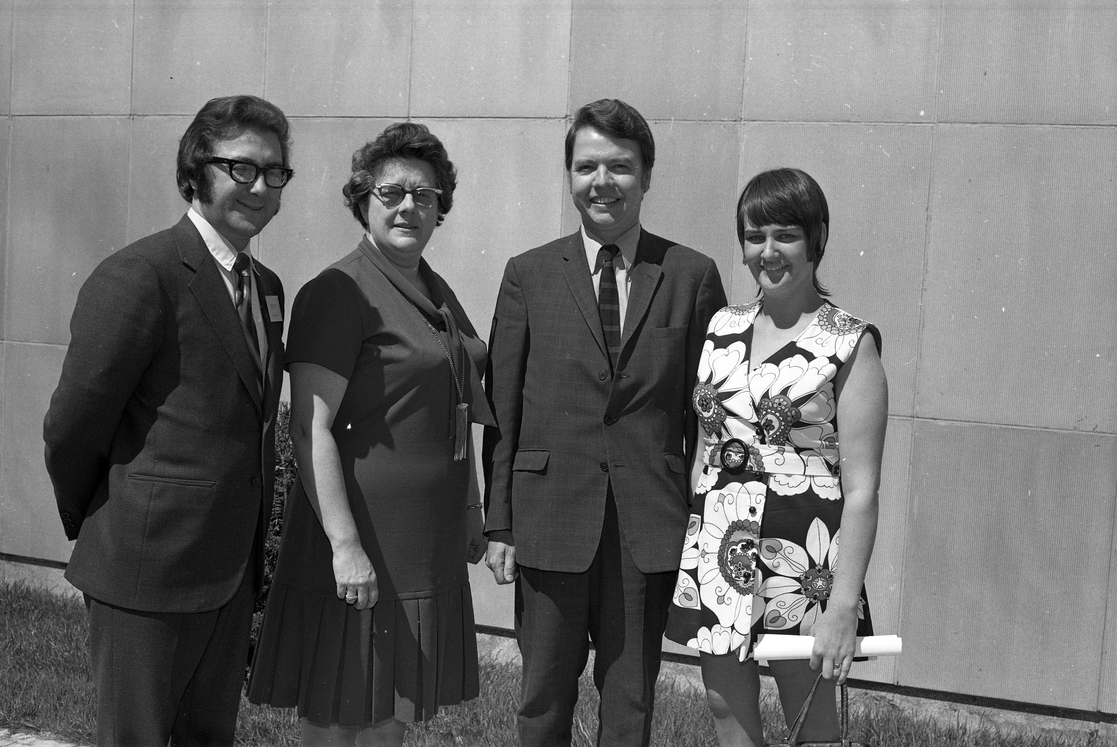Photo en noir et blanc datant environ des années 1970 avec deux hommes et deux femmes, à l'extérieur, devant un mur de béton