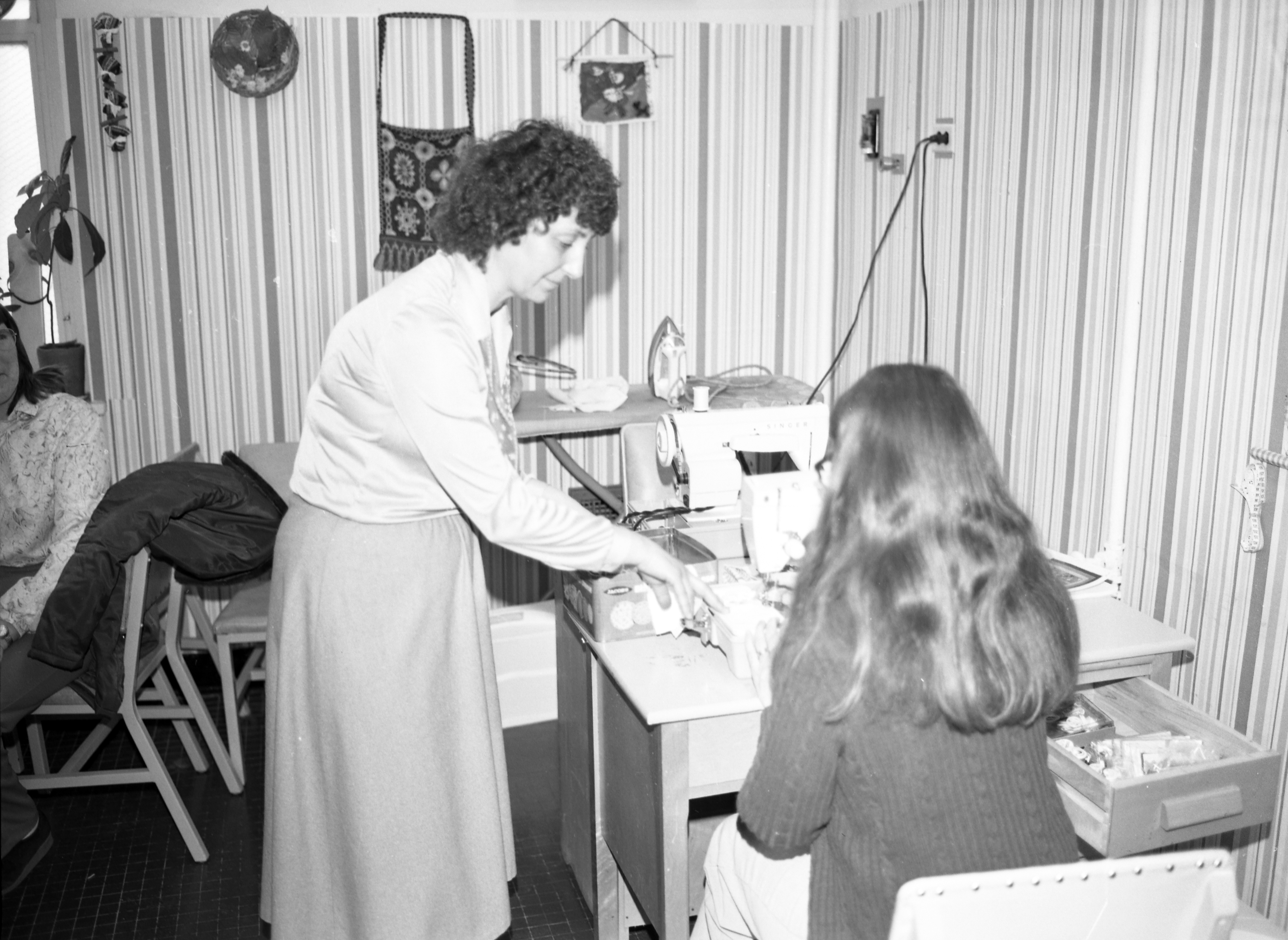black and white photo circa 1970s of woman assisting/directing another woman at sewing maching