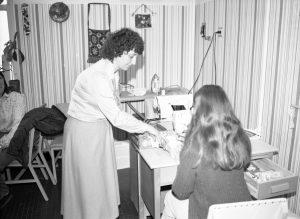 Photo en noir et blanc datant environ des années 1970 avec une femme qui aide une autre femme à utiliser une machine à coudre