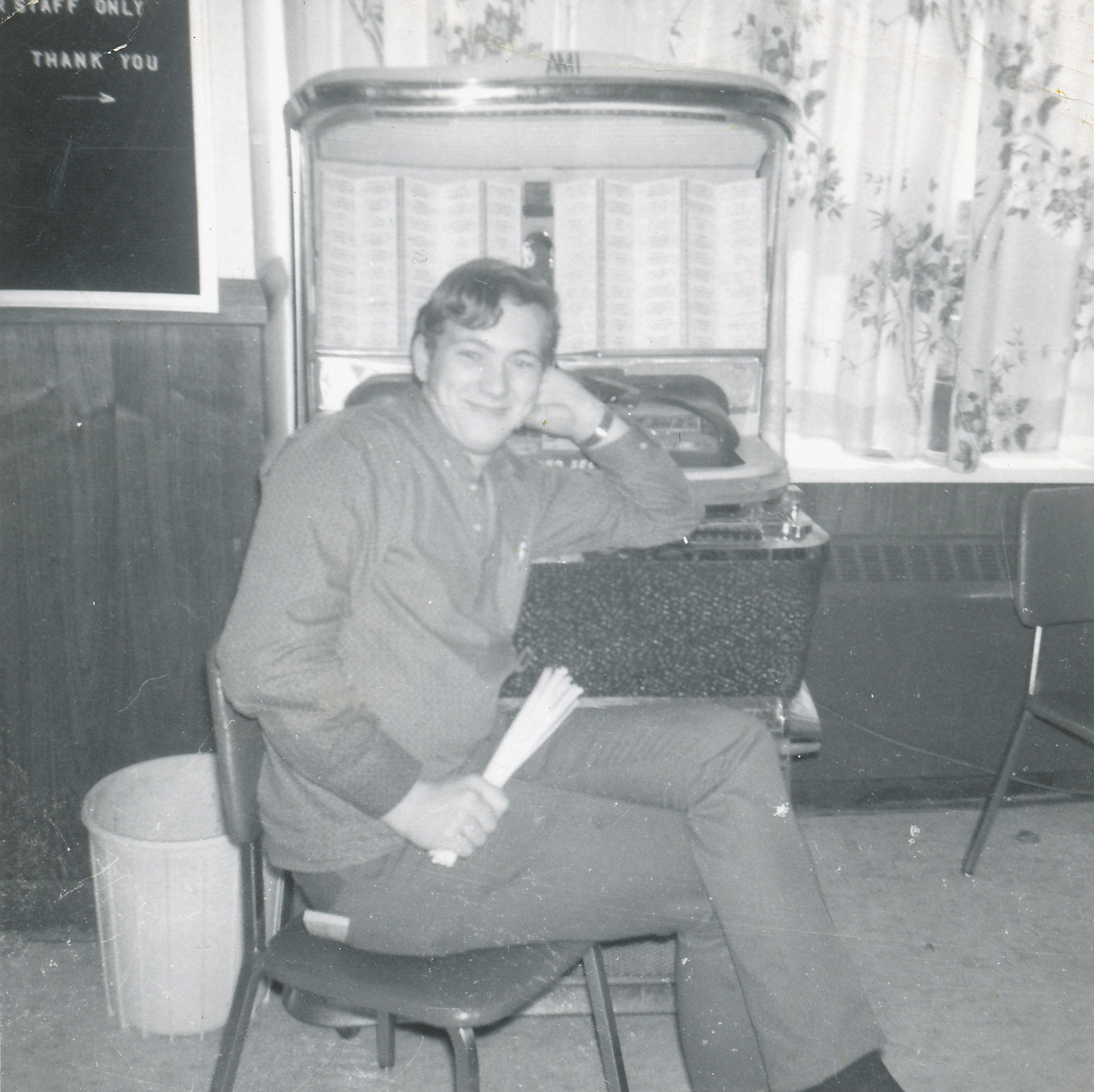 young man sitting on chair in front of jukebook