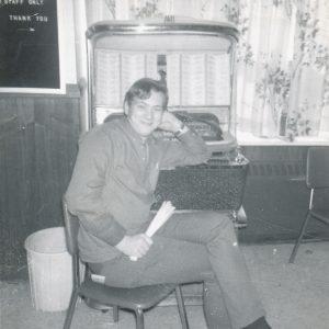Jeune homme avec un look des anneés 1960 assis sur une chaise devant un vieux juke box