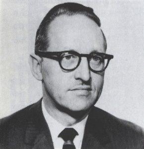 Ancienne photo des années 1950 d'un homme aux cheveux foncés et portant des lunettes