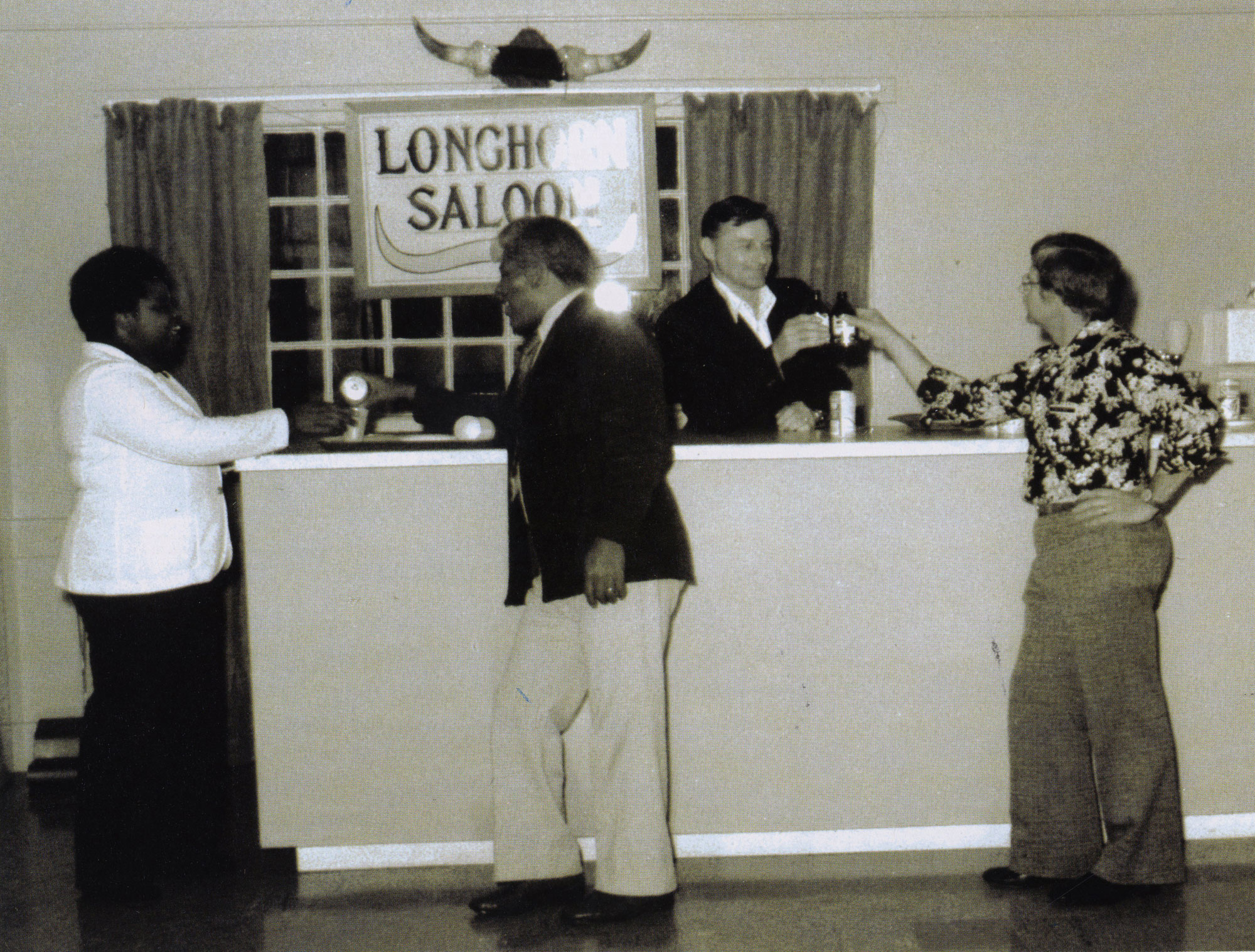 Man behind counter serving drinks and 3 men in front of counter.