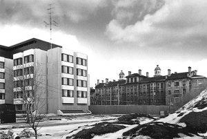 Photographie en noir et blanc des années 1970 représentant à gauche un bâtiment moderne et à droite un édifice institutionnel du 19e siècle