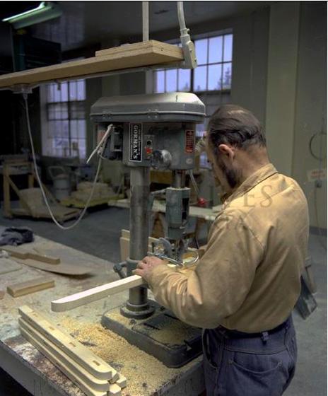 Homme debout devant une table d'un atelier industriel, travaillant sur un projet