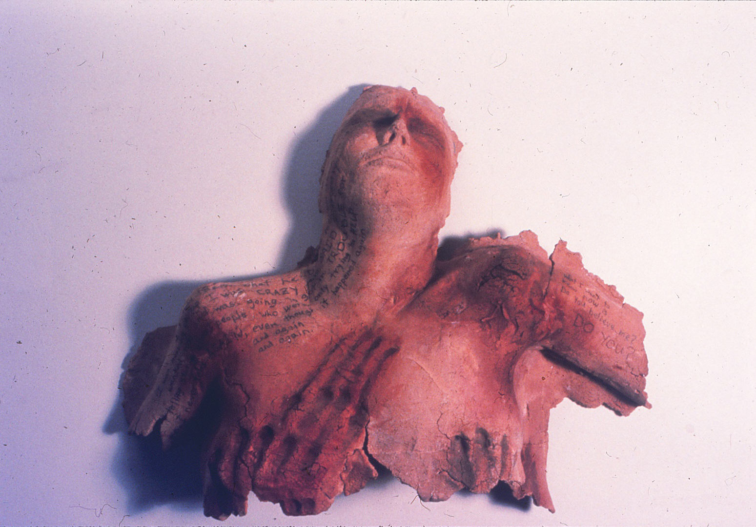 photo of red woman's sculpture head thrown back and shoulders which look burned with messages written on them