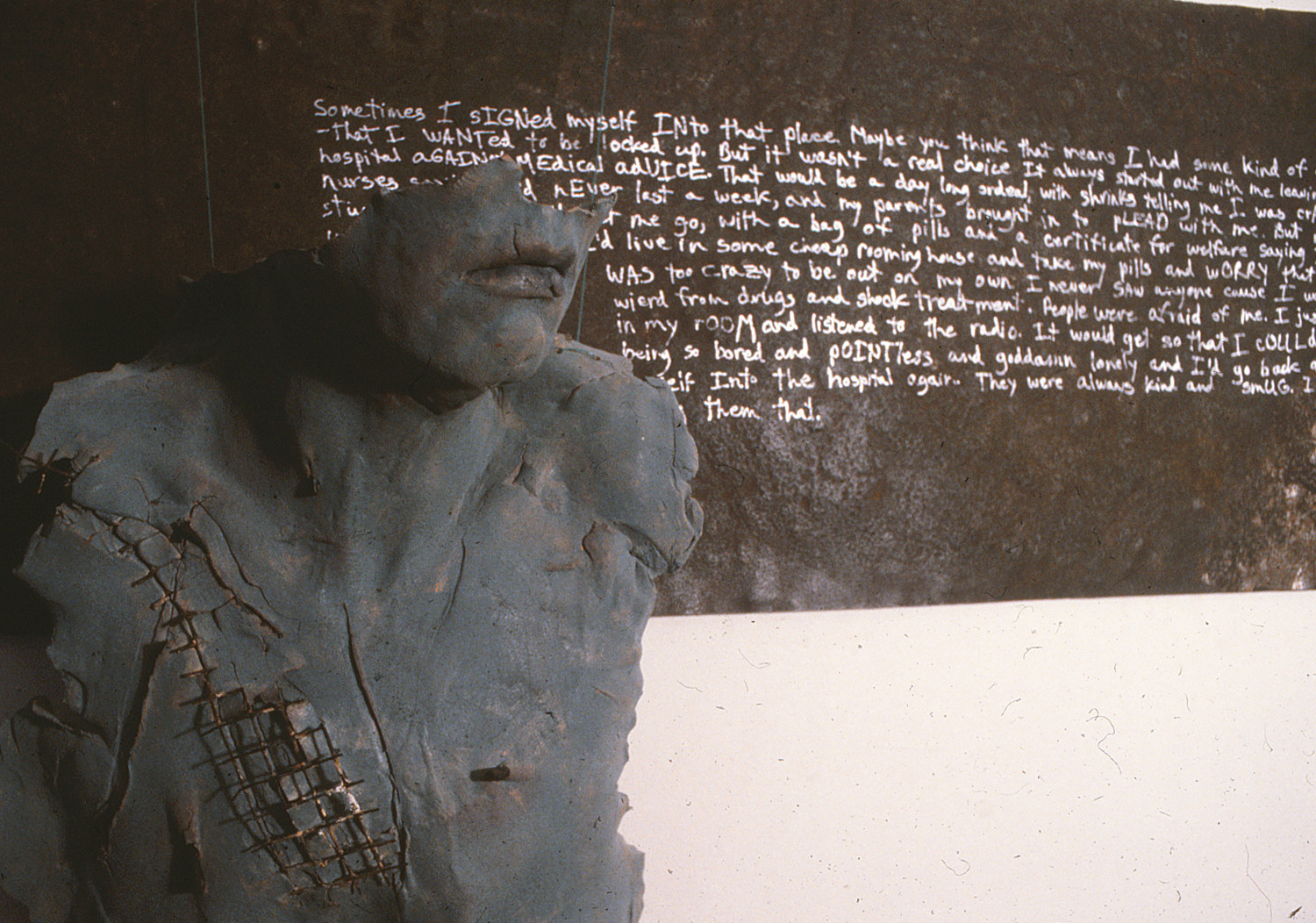 photo of damaged grey naked woman's torso, only portion of face is mouth and it is enduring, message on wall behind