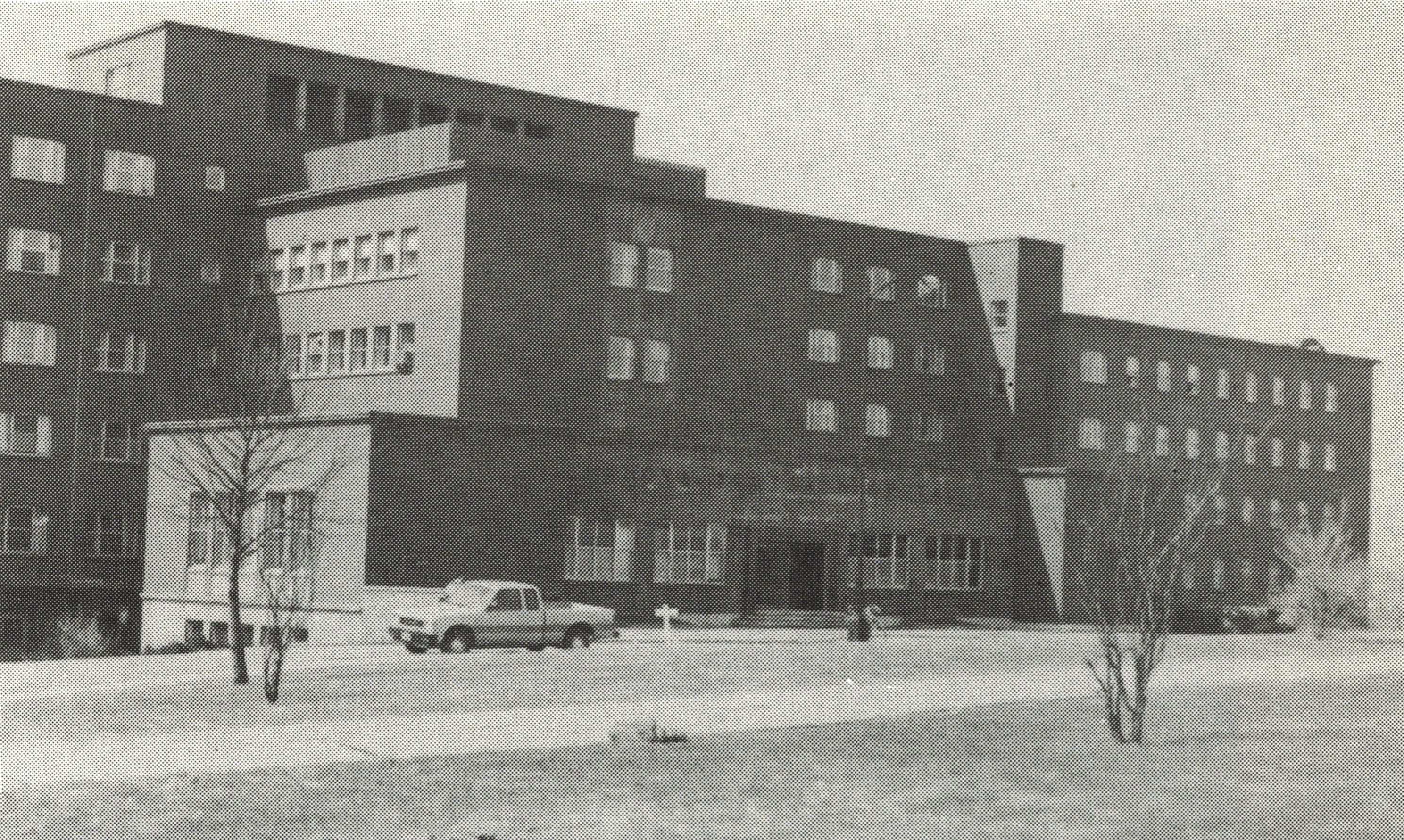 old black and white photo of large hospital building with car in front