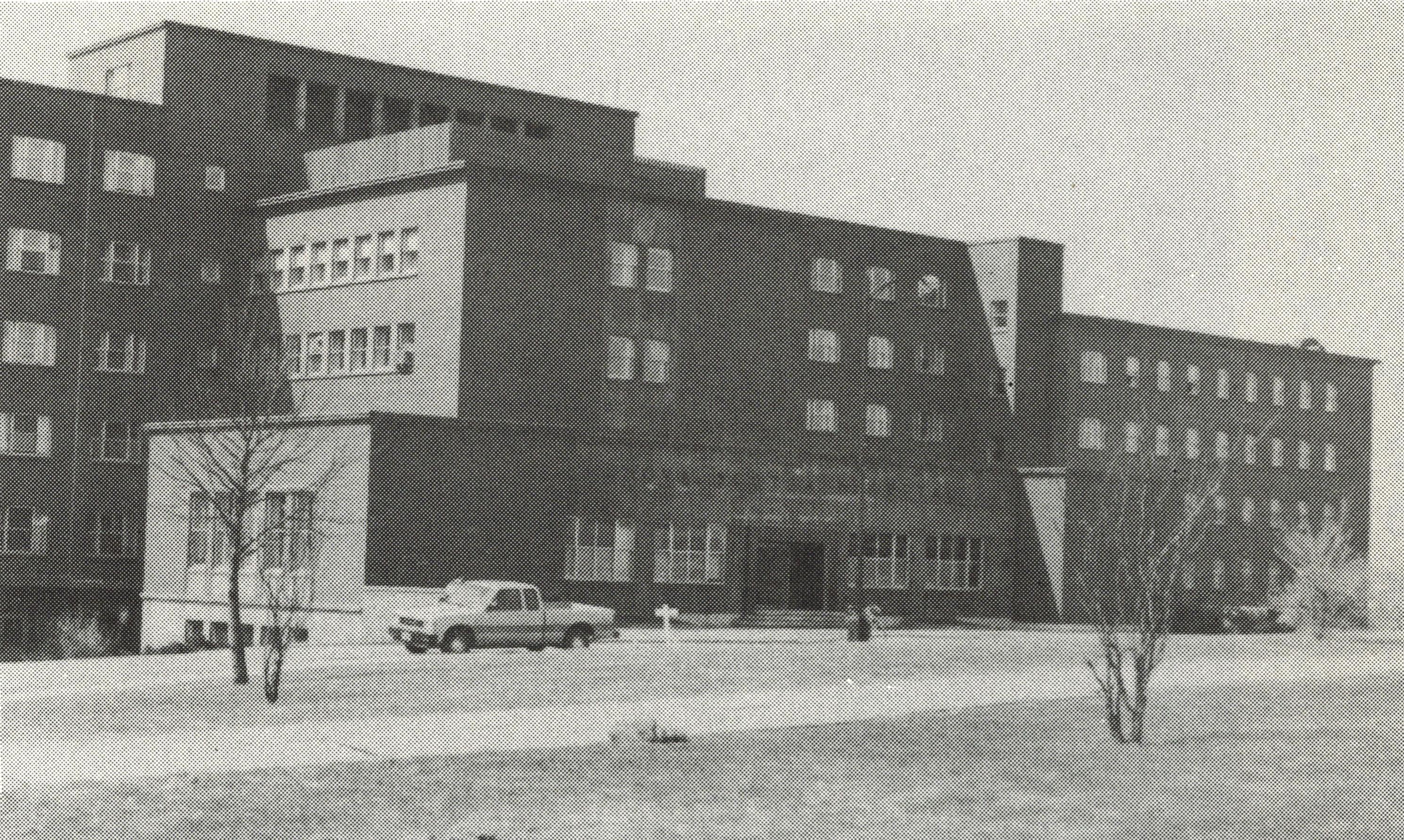 Ancienne photo en noir et blanc d'un grand hôpital avec des voitures stationnées devant