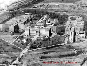 black and white aerial photograph of large institutional complex with main and outlying buildings