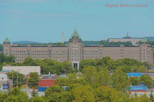 Photo en couleurs d'un immense édifice institutionnel en pierres, entouré de bâtiments commerciaux