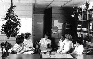 Photographie en noir et blanc des années 1970 représentant un groupe des employés de bureau en réunion