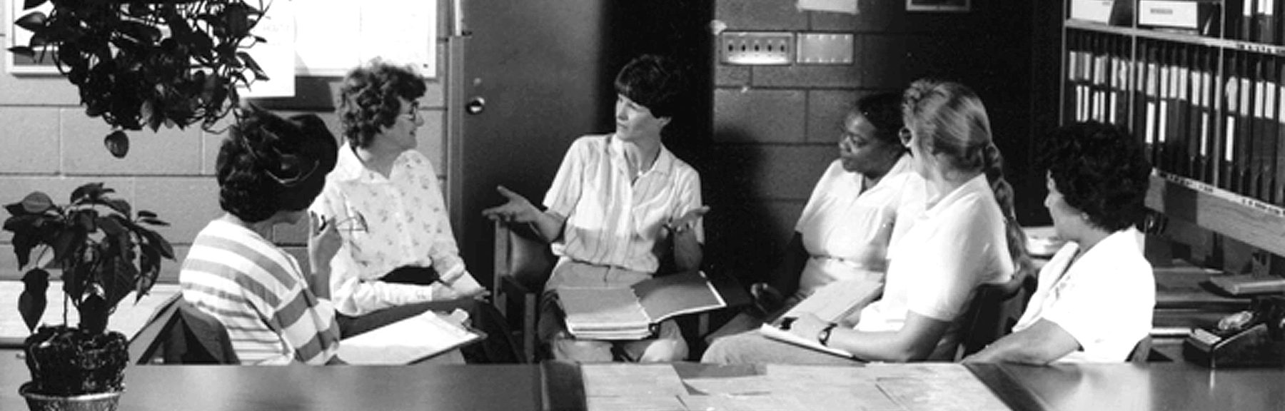 1970s black and white photograph of group of office workers or professional having a meeting or discussion in office setting