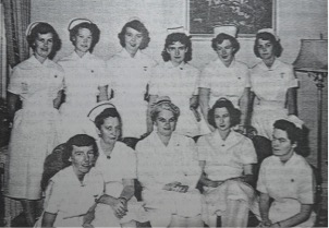 group of nurses wearing uniforms and caps, circa 1950s
