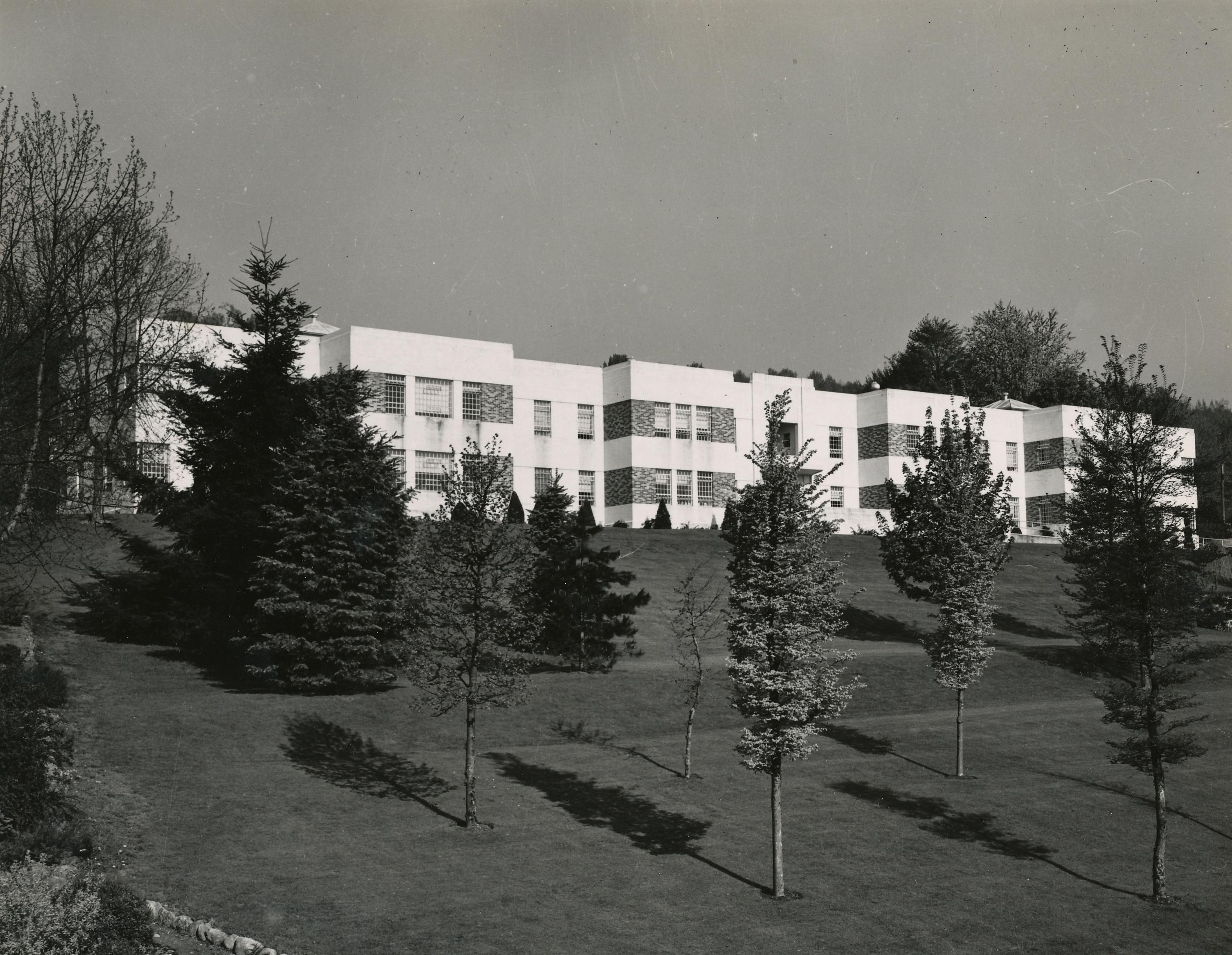 Édifice institutionnel qui ressemble ayant la forme d'un bloc d'appartements blanc de deux étages