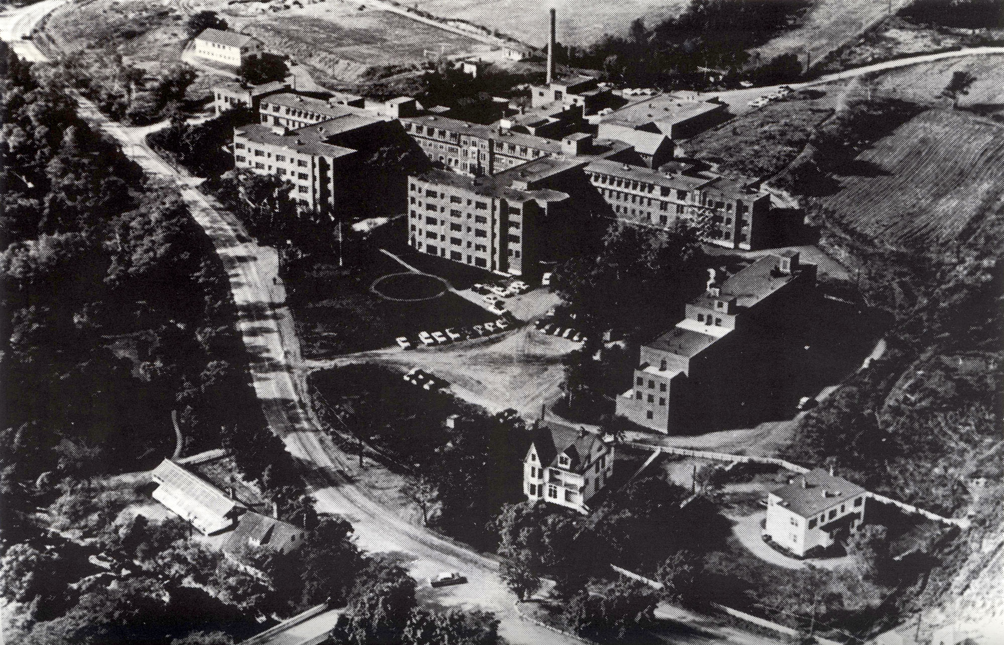 aerial black and white photograph of institutional complex with road, large main building and smaller surrounding buildings