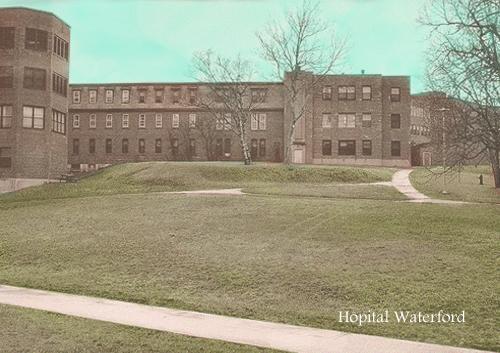 Photo couleur de l'entrée extérieur d'un édifice institutionnel de brique à l'architecture d'après-guerre