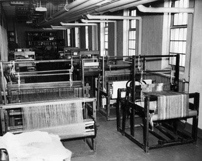 Photo en noir et blanc d'un atelier avec plusieurs métiers à tisser