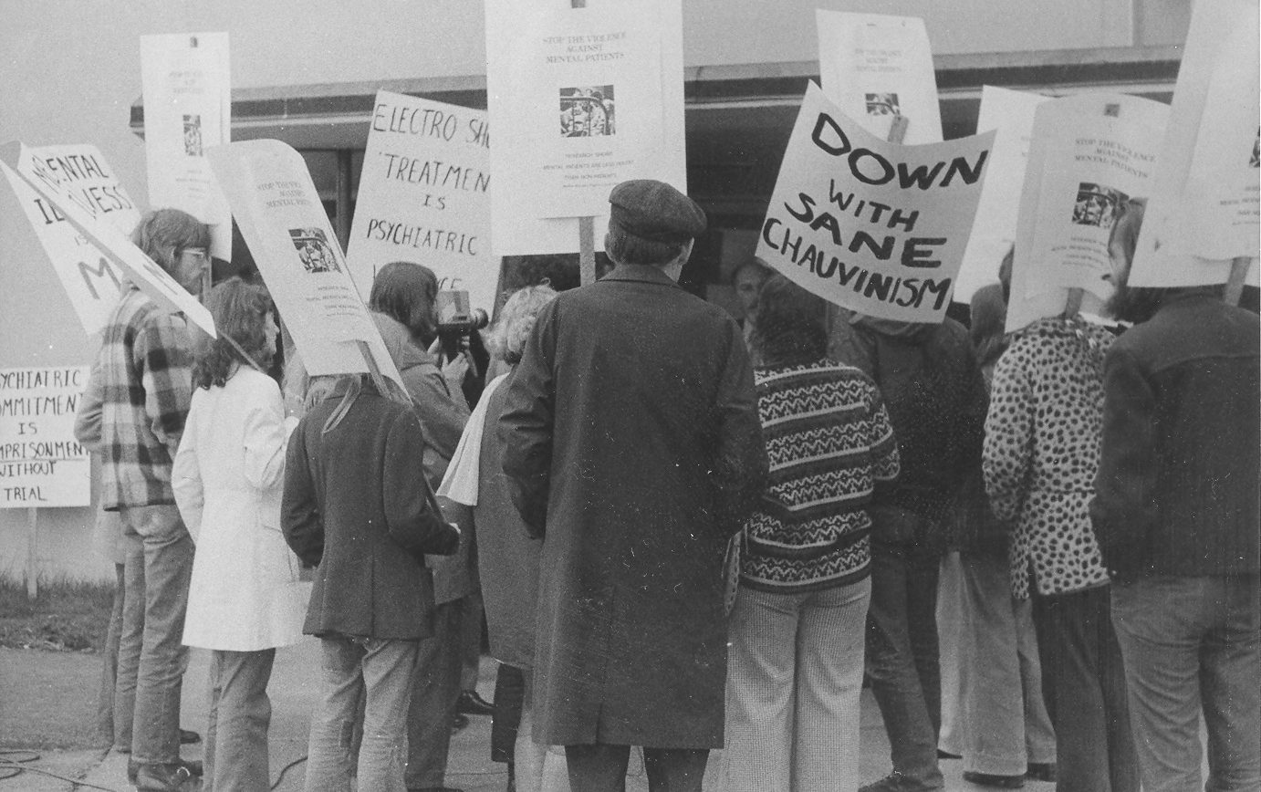 small crowd of 1970s protesters with signs