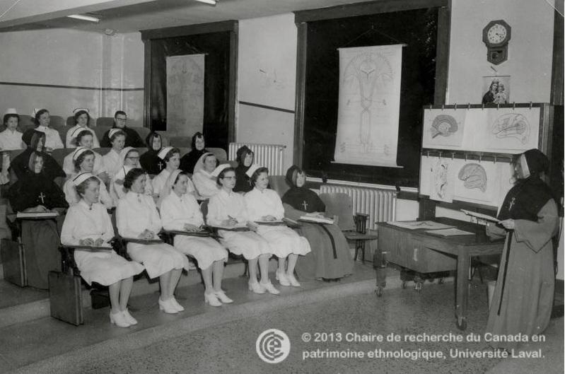 Photo en noir et blanc représentant une religieuse s'adressant à une classe composée de femmes en tenue d'infirmière et de femmes en tenue de religieuse