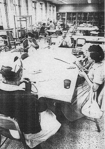 Ancienne photo en noir et blanc représentant des femmes et des hommes dans un atelier institutionel en train de tricoter