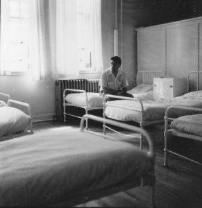 Ancienne photo en noir et blanc représentant un homme assis sur un lit dans un dortoir avec de grandes fenêtres