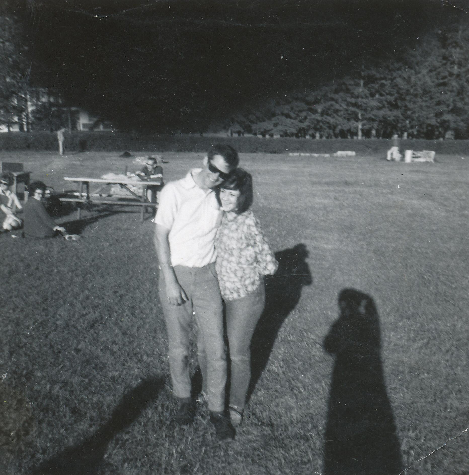 Jeune homme et jeune femme marchant dans un parc collés l'un contre l'autre, avec vêtements des années 1960