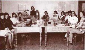 Photo en noir et blanc d'un groupe d'hommes et de femmes réuni autour d'une grande table