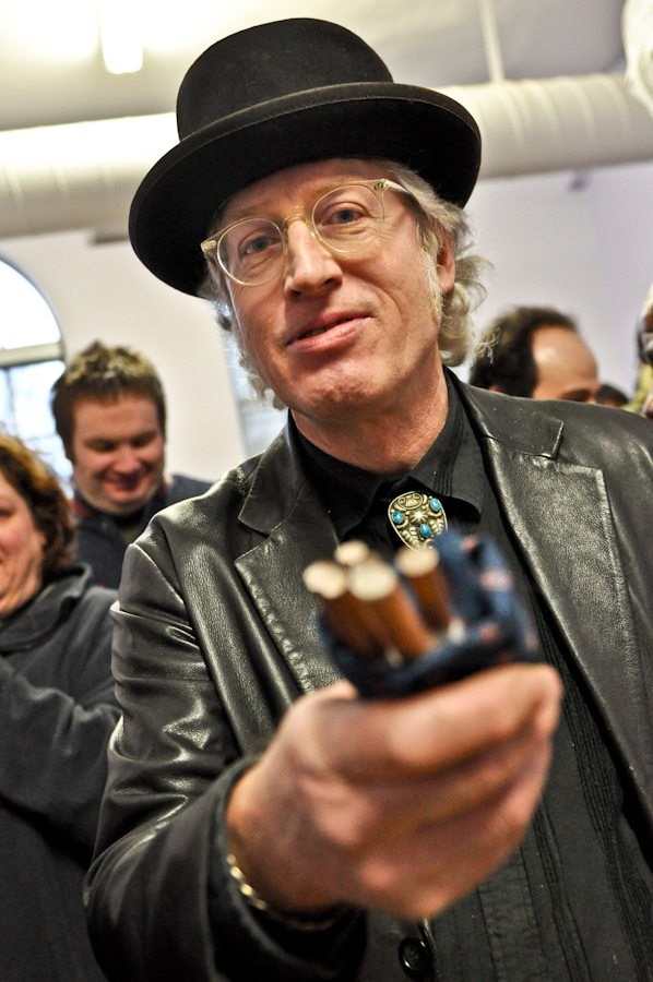 man with glasses and black hat holding out a pack of cigarettes