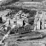Photo en noir et blanc d'une vue aérienne d'un vaste complexe composé de plusieurs bâtiments institutionnels