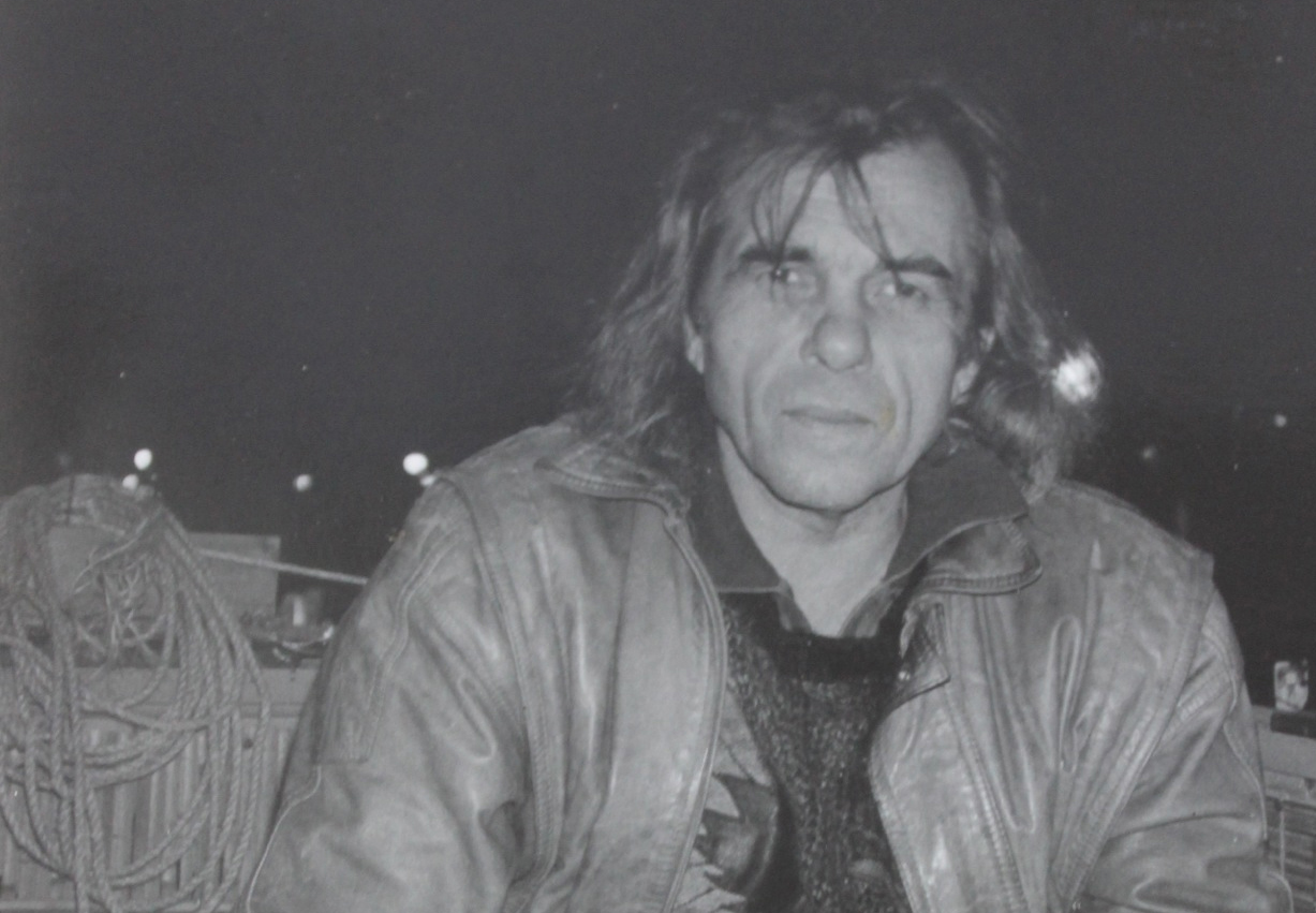 black and white photo of older man with long hair