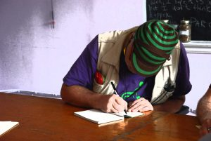 colour photo of person in green cap sitting at table intently writing