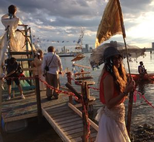 colour photo of man and other people on pier, carnival/party scene