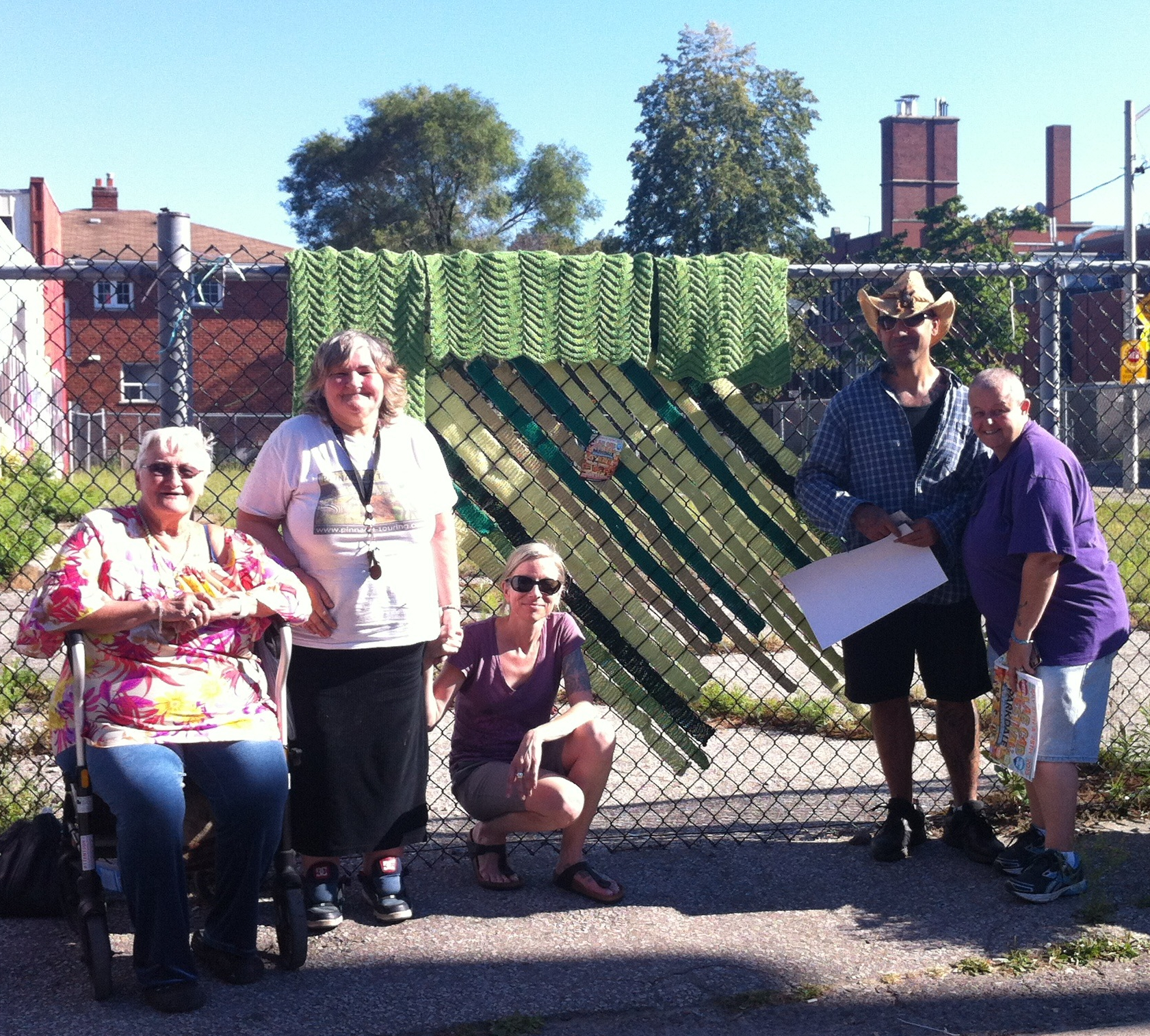 colour photo of smiling group of people standing outside against fence with knitted blanket hung on it
