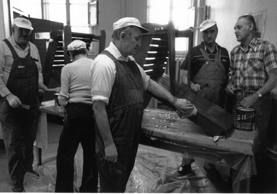 Photo en noir et blanc d'un groupe d'hommes en train de vernir des chaises dans un atelier