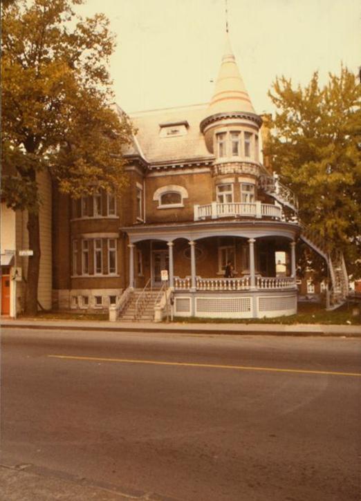 Photo en couleurs d'une maison à l'architecture victorienne en milieu urbain