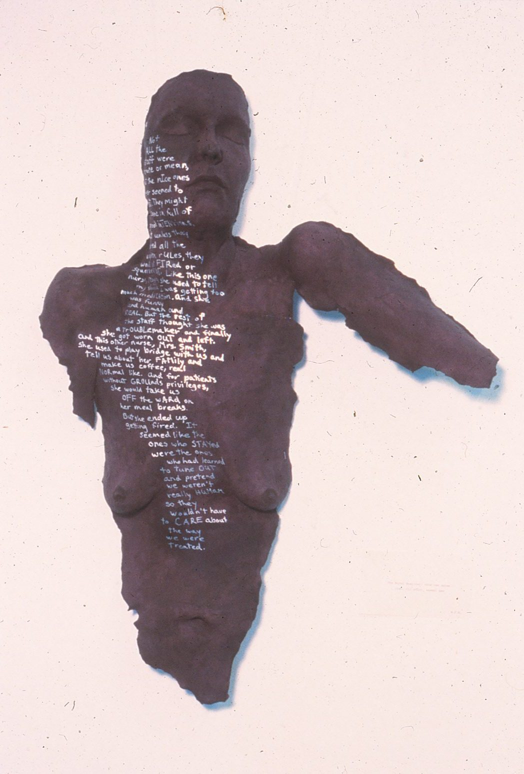 brown woman's torso with silver writing on it and face