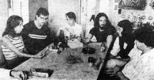 group of 1970s young people sitting around a table