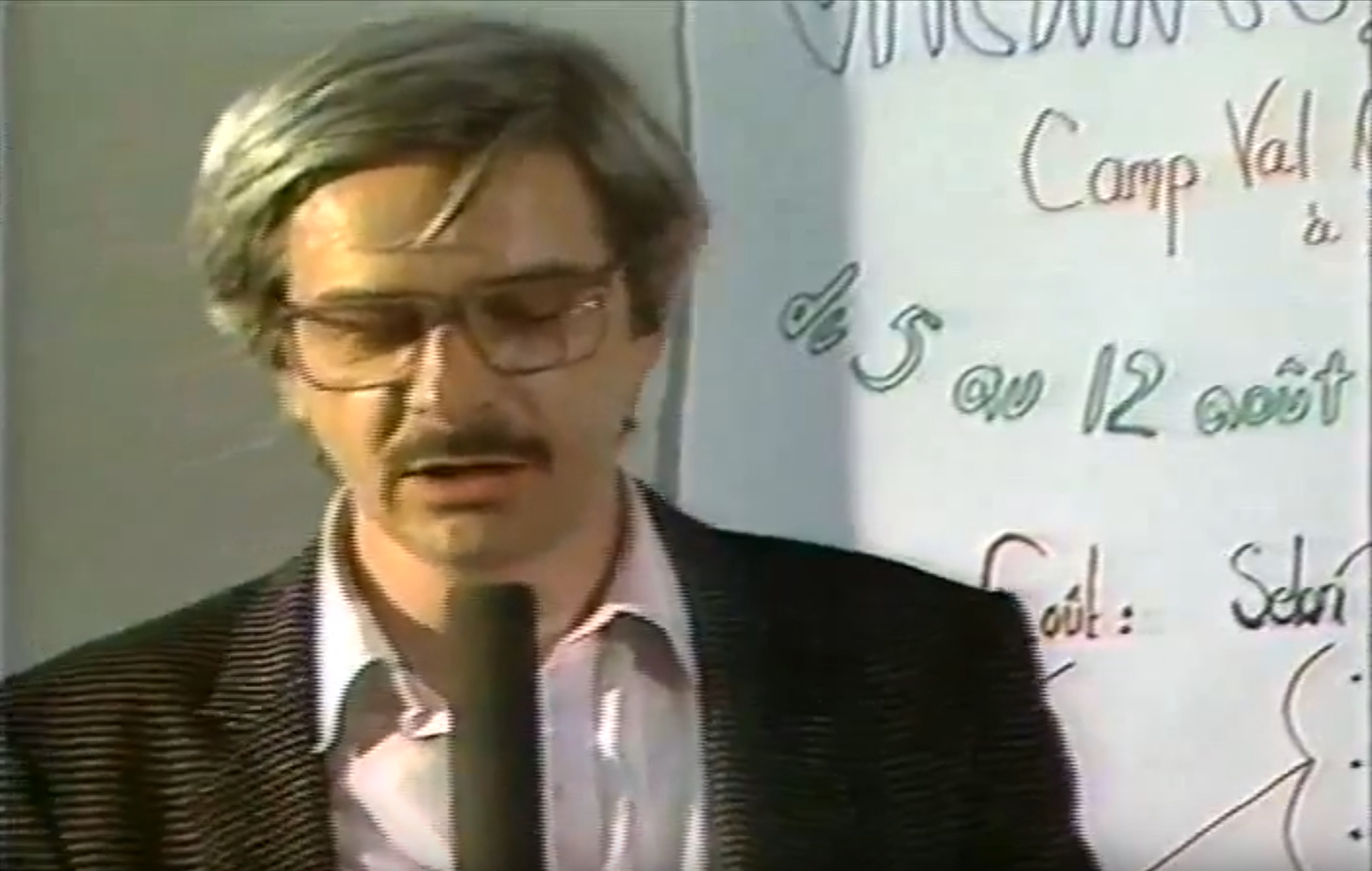 man with glasses speaking into a microphone