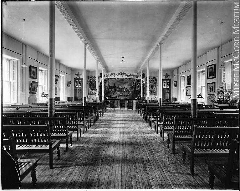 Rectangular room in which there are several rows of benches in front of a stage