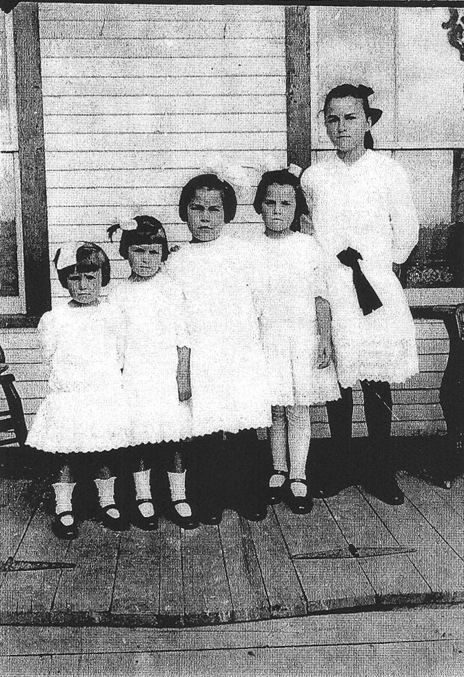 Cinq petites filles les unes à côté des autres de la plus petite à la plus grande toutes vêtues d'une robe blanche